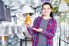 Girl bragging about buying a lamp Stock Photos