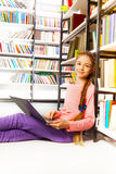 Girl with braid holds laptop in library. Girl with braid holds laptop and sits on the floor near bookshelf in library Stock Photo