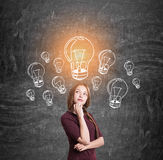 Girl with a braid and many light bulbs Stock Photography