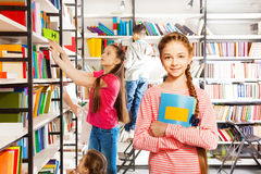 Girl with braid stands, holds notebook in library Stock Photo