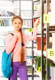 Girl with braid stands near bookshelf Royalty Free Stock Image