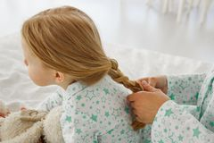 The girl is braided with a pigtail. Mom plaits a pigtail to her daughter. Make a haircut royalty free stock images