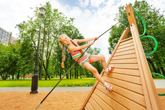 Girl with braids climbs on wooden construction Stock Images