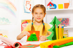 Girl with braids holds New Year and sits at table Royalty Free Stock Images
