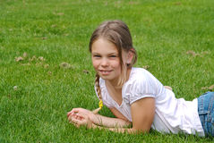 Girl with braids lying in grass Stock Photography