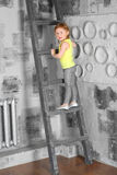 Girl with braids stands on a wooden ladder Royalty Free Stock Image