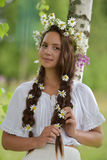 Girl with braids and a wreath of daisies Royalty Free Stock Images