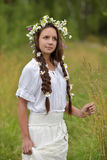 Girl with braids and a wreath of daisies. Girl with braids and daisies in her hair Royalty Free Stock Photo