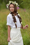 Girl with braids and a wreath of daisies Stock Photos