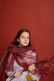 Girl with a branch of autumn leaves Stock Images