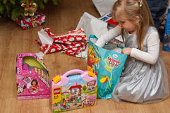 Girl with branded toys under Christmas tree Stock Image