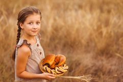 Girl with bread and buns in basket. Child is holding a lot of loaves in hands in the field. Girl with freshly baked buns ad loaves in the basket in the hands stock images