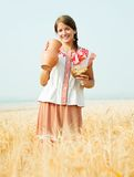 Girl in with bread and jug at  field Royalty Free Stock Photography