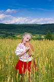 Girl with bread in the wheat field Stock Photography