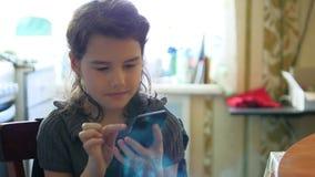 Girl breakfast in the kitchen playing smartphone online social media games. Girl breakfast in kitchen playing smartphone online social media games stock footage