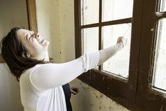 Girl breaking window Royalty Free Stock Image