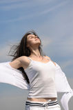 Girl breathes in fresh air on a blue sky background. She stands her arms to the side and her hair fluttering in the wind. She is wearing in a white loose Stock Photos