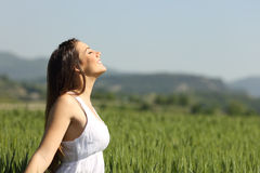 Girl breathing fresh air with white dress. In a green wheat meadow Royalty Free Stock Photos