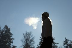 Girl breathing warm air during cold day. Silhouette of a woman with hat breathing warm air during a cold winter morning. Selective focus used royalty free stock image