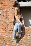 Girl on brick wall Royalty Free Stock Image