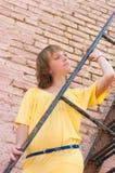 The girl at a brick wall Stock Images