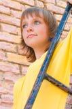 The girl at a brick wall Stock Image