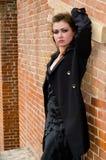 The girl at a brick wall Stock Photography