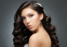 Girl with bridal hairstyle and makeup. Portrait of a pretty young woman with a beautiful bridal hairstyle and makeup. Brunette with long wavy hair Stock Photos