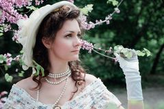 Girl bride in a hat near a tree royalty free stock image