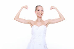 Girl bride shows her muscles strength and power. Woman bride in wedding dress shows her muscles flexing biceps clenching fist isolated on white background Royalty Free Stock Photo