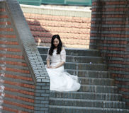 Girl bride in wedding dress. A Chinese Bride with white wedding dress sit on the steps. at ShangHai SongJiang Thames Town Royalty Free Stock Photos