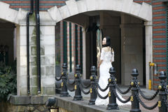 Girl bride in wedding dress. A Chinese Bride with white wedding dress stand near the Iron fence. at ShangHai SongJiang Thames Town Stock Photo