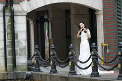 Girl bride in wedding dress. A Chinese Bride with white wedding dress stand near the Iron fence. at ShangHai SongJiang Thames Town Stock Photos