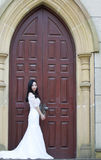 Girl bride in wedding dress. A Chinese Bride with white wedding dress stand near the old red door. at ShangHai SongJiang Thames Town Stock Photo