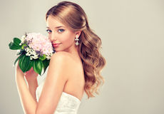 Girl bride in wedding dress with elegant hairstyle. Girl bride in wedding dress with elegant hairstyle and with a wedding bouquet Royalty Free Stock Photos