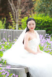 Girl bride in wedding dress with elegant hairstyle, with white wedding dress Sitting on the bench next to the fence Royalty Free Stock Photos