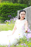 Girl bride in wedding dress with elegant hairstyle, with white wedding dress Sitting Leaning against the fence Royalty Free Stock Photos