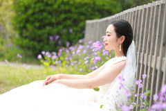 Girl bride in wedding dress with elegant hairstyle, with white wedding dress Sitting Leaning against the fence Royalty Free Stock Photography