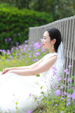 Girl bride in wedding dress with elegant hairstyle, with white wedding dress Sitting Leaning against the fence Stock Photos