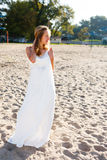 Girl bride in a white dress on the sunny beach Royalty Free Stock Images
