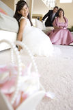 Girl (8-10), in bridesmaid�s dress, sitting on carpet in living room, senior couple looking on, wedding gift in foreground, smil Stock Image