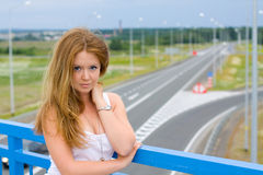Girl on a Bridge. The girl on the background of the highway Royalty Free Stock Photos