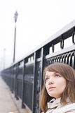 Girl on a bridge. Close-up of young pretty girl sit on a bridge with thoughtful look Royalty Free Stock Photography