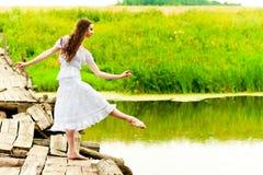 Girl on the bridge balances on one leg Stock Photo