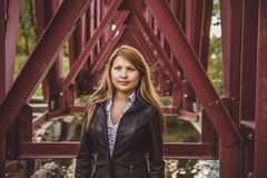 The girl at the bridge piles. Asian girl standing in a leather jacket of bridge piles Stock Photo
