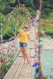 Girl on the bridge. Rope suspension bridge. Colored rope.  Stock Images