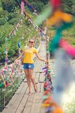 Girl on the bridge. Rope suspension bridge. Colored rope.  Stock Photo