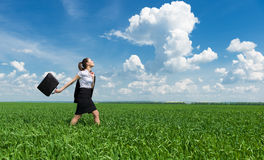 Girl with a briefcase walking on grass Royalty Free Stock Images