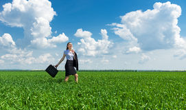 Girl with a briefcase walking on grass Stock Photography