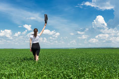 Girl with a briefcase walking on grass Royalty Free Stock Photography